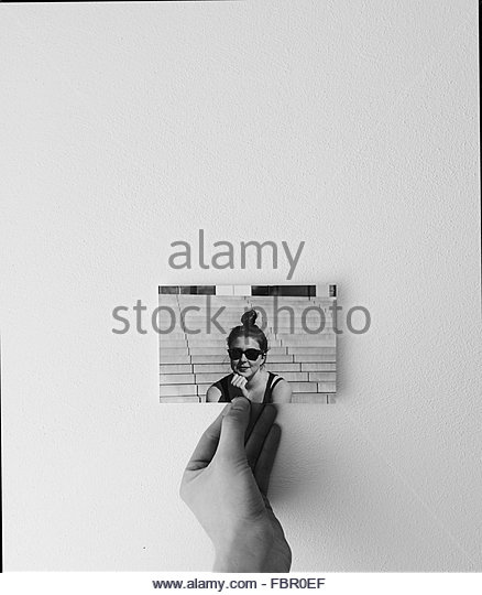 Close-Up Of Hand Holding Photograph Of A Woman - Stock Image