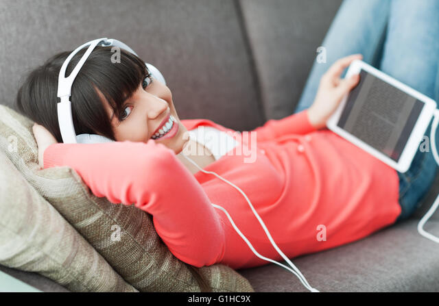Smiling young woman relaxing at home on the couch, she is wearing headphones, using a digital tablet and watching - Stock-Bilder