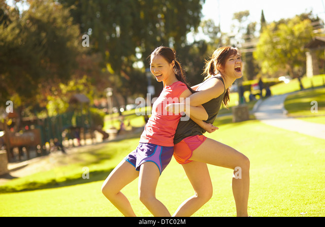 Two young women arm in arm and back to back in park - Stock Image