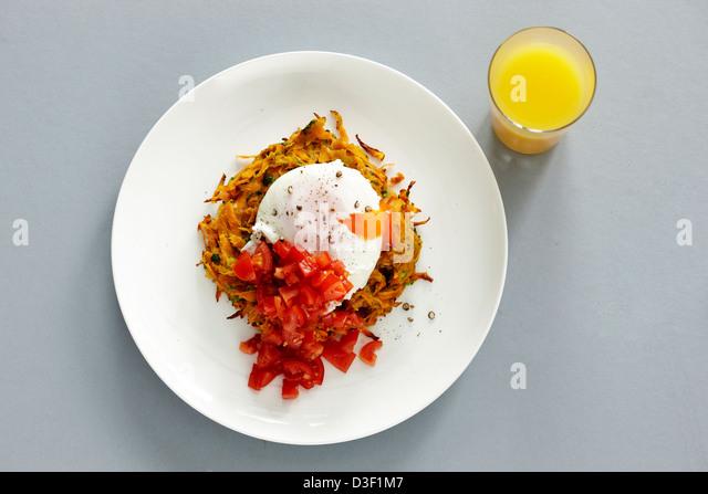 Poached egg sweet potato hash orange juice tomato - Stock Image