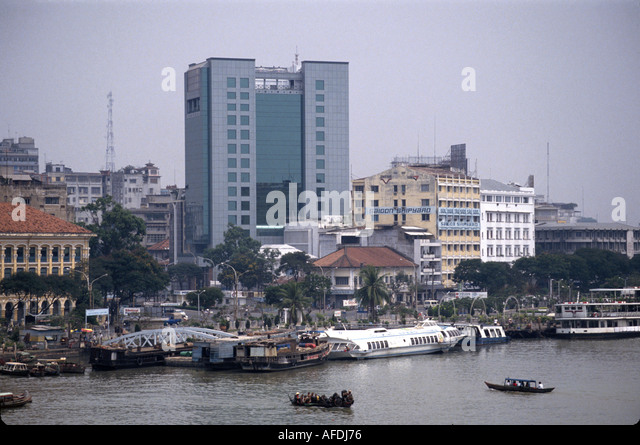 Vietnam Saigon Ho Chi Minh City downtown skyline office buildings boats water taxi river - Stock Image