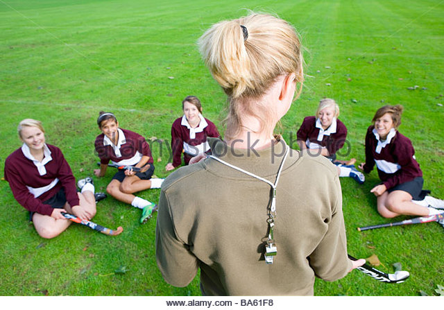 Coach standing before teenage girl field hockey team - Stock Image