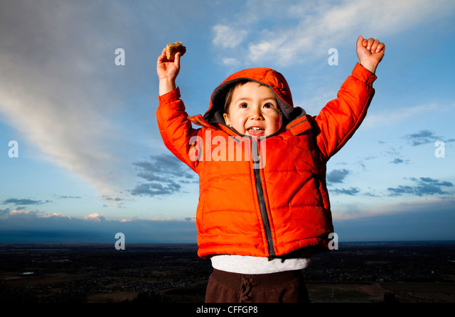 A young boy lifts hands in excitement outdoors in Fort Collins, Colorado. - Stock Image