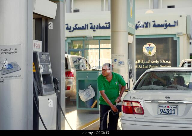 Wadi Al Sail Petrol Station, Riffa, Bahrain. Man filling car from fuel pump on service court - Stock Image