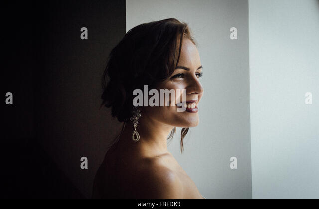 Thoughtful Smiling Young Woman Against Wall - Stock Image