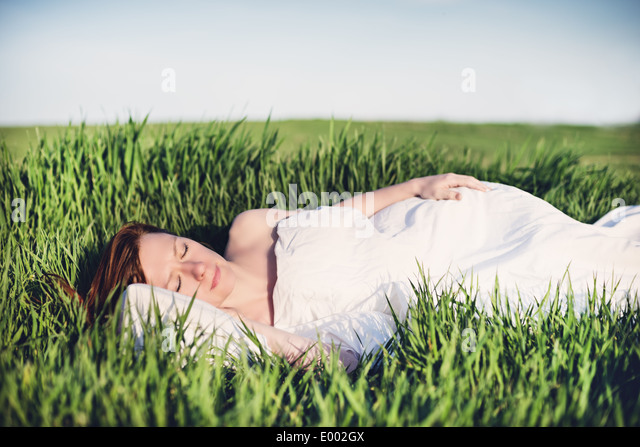 Young woman sleeping on soft pillow in fresh spring grass - Stock-Bilder