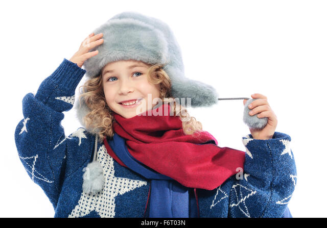 Girl wearing winter fur hat.Portrait of a child dressed in winter hat and mom's knitted warm sweater.On her - Stock Image