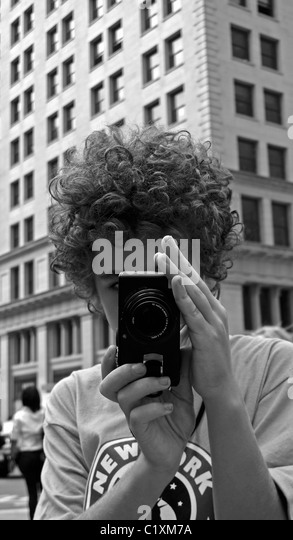 Young New York tourist taking photographs with a camera. - Stock Image