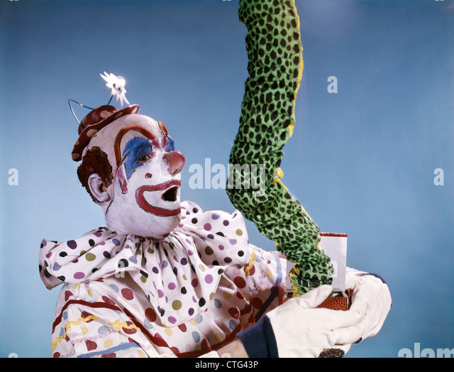 1960s SURPRISED CLOWN POLKA DOT COSTUME LETTING SNAKE LIZARD GREEN THING JUMP OUT OF BOX - Stock Image