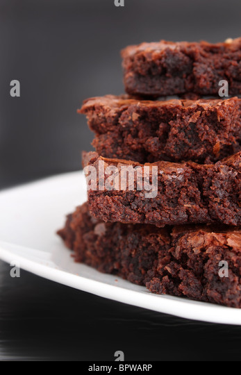 Pile of chocolate fudge brownies on a plate with a grey background (short depth of field) - Stock Image