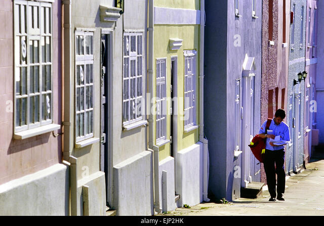 Male postman delivering mail. Hastings. East Sussex. England. UK - Stock Image