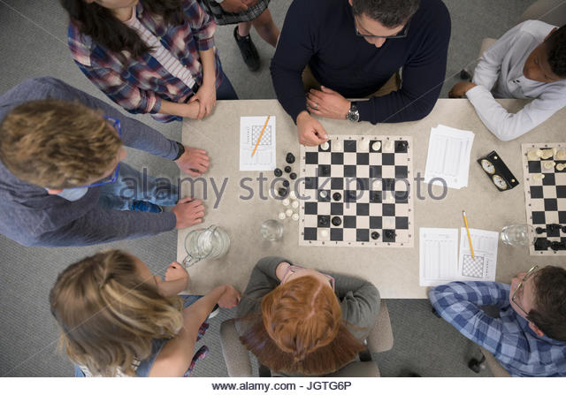 Teacher and middle school students playing chess in chess club - Stock Image