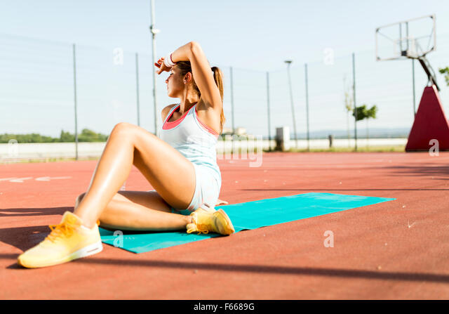 Exhausted young beautiful woman taking a rest on a hot summer day - Stock Image