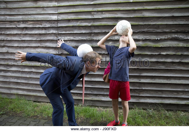 Businessman Father Playing Soccer With Teenage Son - Stock-Bilder