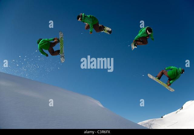 Snowboarder dangerous free ride jump - Stock Image