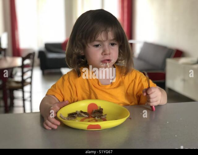 Toddler eating at home - Stock Image
