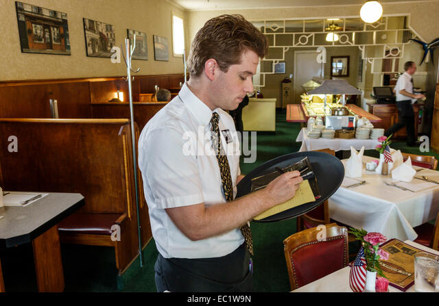Illinois Litchfield Historic Route 66 The Ariston Cafe restaurant inside interior man waiter writing order employee - Stock Image