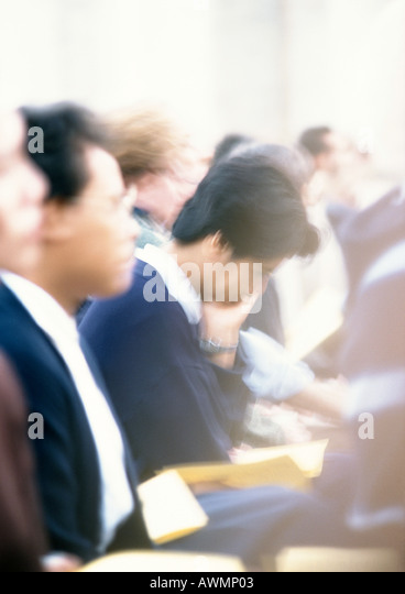People sitting side by side during mass, side view, close-up, blurred - Stock Image