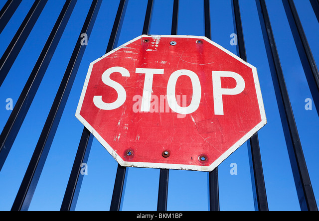 stop sign mounted on iron fence - Stock Image