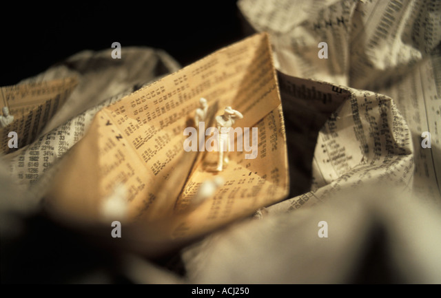 Figures on a paper boat made from a newspaper with stock market rates. - Stock-Bilder