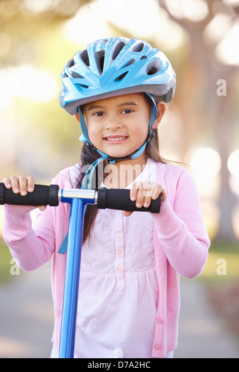 Girl Wearing Safety Helmet Riding Scooter - Stock Image