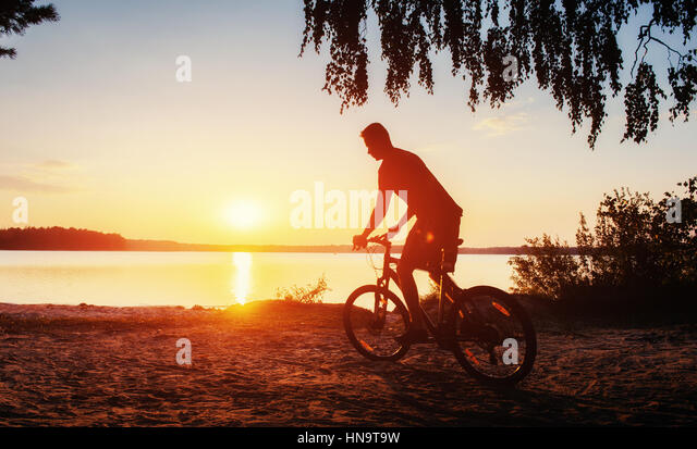 boy on a bicycle at sunset - Stock Image
