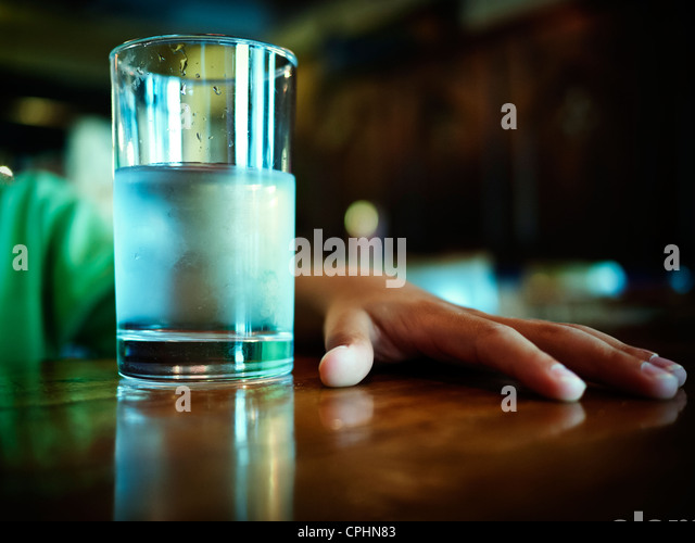 Glass of iced water and boy's hand on table - Stock Image