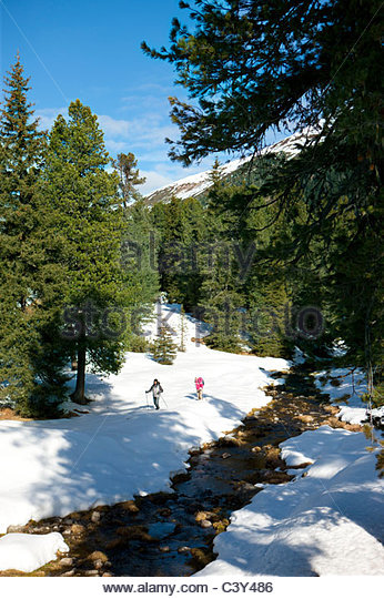 Couple exploring snow covered wilderness - Stock Image