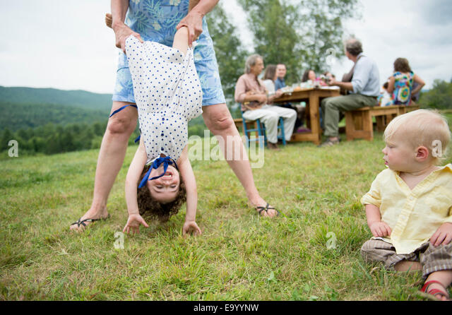 Female family member playfully holding toddler by legs at family gathering, outdoors - Stock-Bilder
