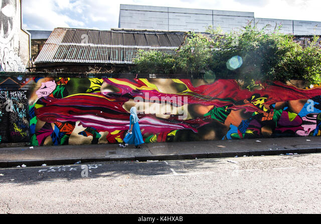 Muslim woman in blue veil face obscured and blurry walks past a vivid, brightly coloured street mural on Sclater - Stock Image