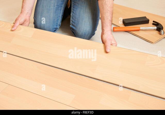 Man Laying Laminate Flooring - Stock Image