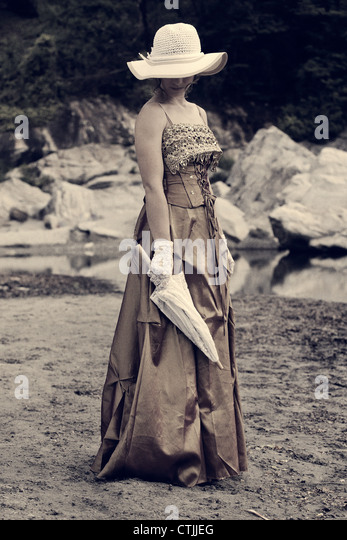 a young woman in a romantic period dress standing on the shore of a lake - Stock Image
