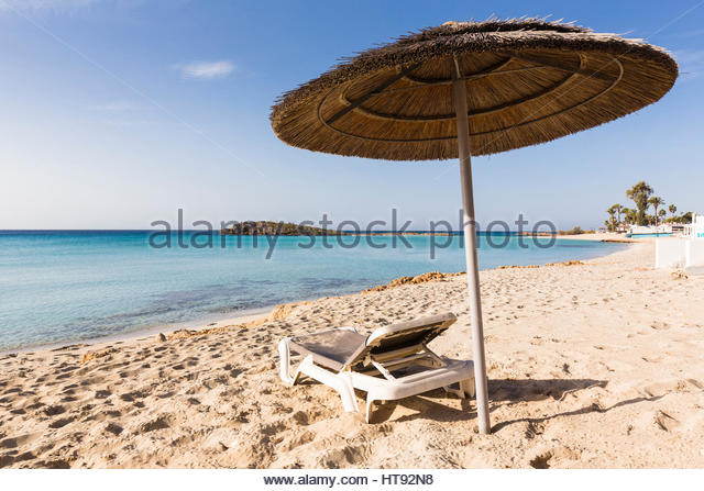 Beach umbrella and lounge chair on Nissi Beach at the Nissi Beach Resort in Agia Napa, Cyprus - Stock Image