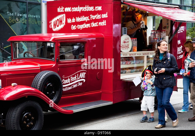 Pedestrians walk by a red food truck in the street;Dublin county dublin ireland - Stock Image