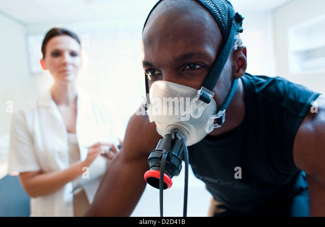 MODEL RELEASED Performance testing Athlete riding an exercise bike while his performance and oxygen consumption - Stock Image
