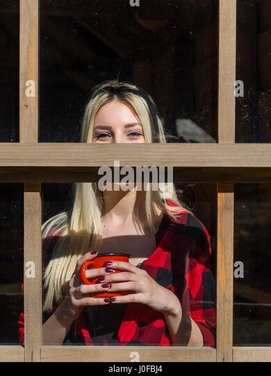 Beautiful blonde young woman behind window cup mug coffee tea in hands hand frames framed glass - Stock Image