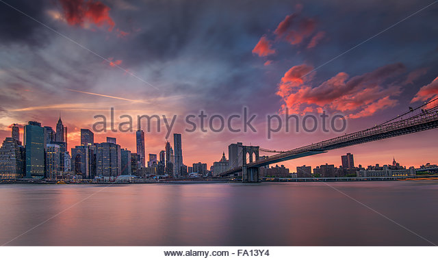 View of New York City or Manhattan Skyline and Brooklyn Bridge from the Brooklyn Promenade at sunset with pink clouds - Stock Image