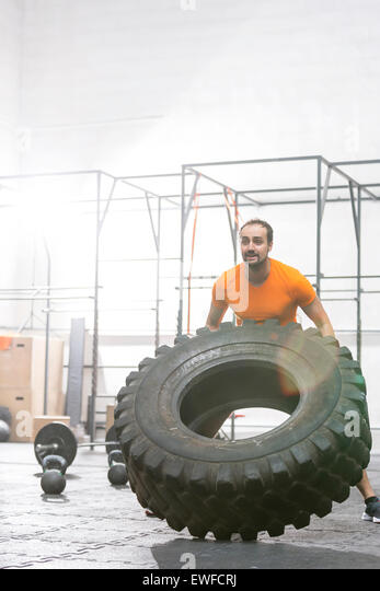 Dedicated man flipping tire in crossfit gym - Stock Image