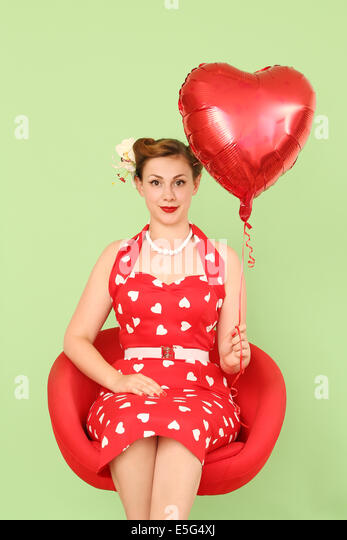 Woman in red dress holding heart shaped balloon - Stock Image