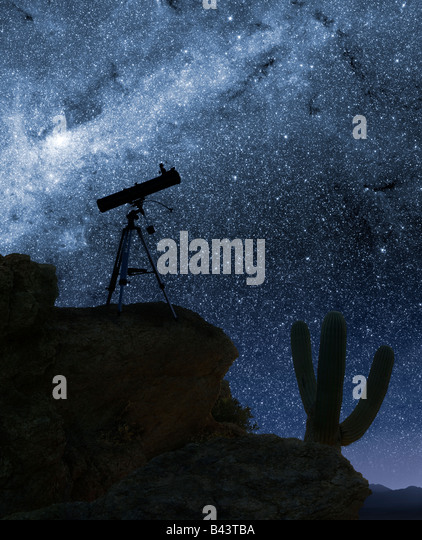 A telescope pointed at the stars from a desert mountain location - Stock Image