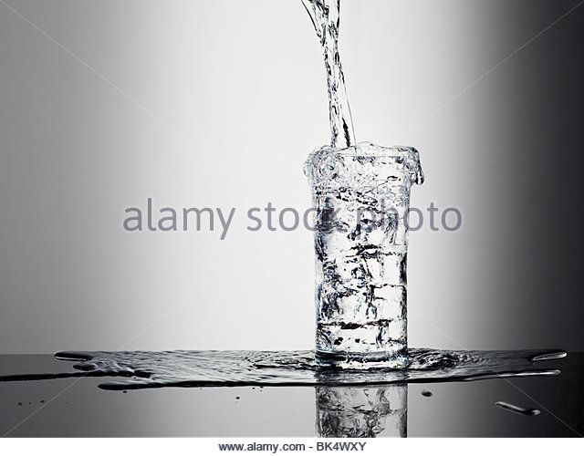 Water pouring into glass and overflowing - Stock Image