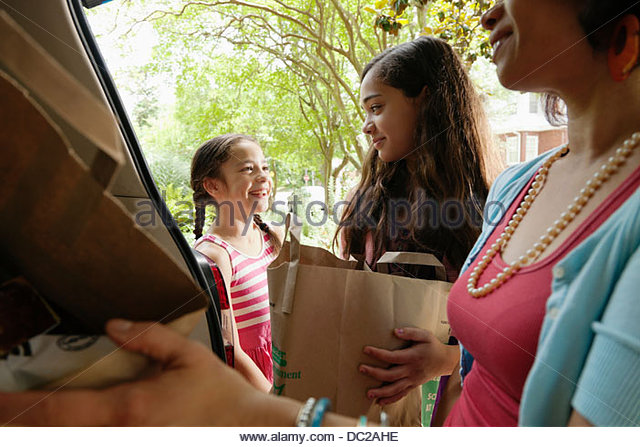 Mother and daughters unloading shopping bags - Stock-Bilder