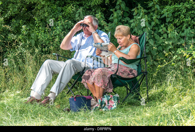 Old / elderly / senior couple relaxing in the warm sunshine, on portable, lightweight chairs, at Box Hill, Surrey, - Stock Image