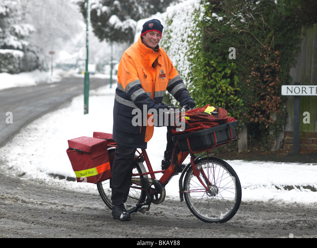 Postman On Bicycle In The Snow Surrey England - Stock Image