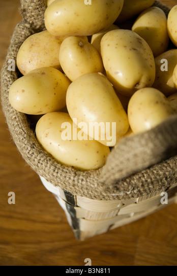 Potatoes in jute bag, elevated view - Stock Image