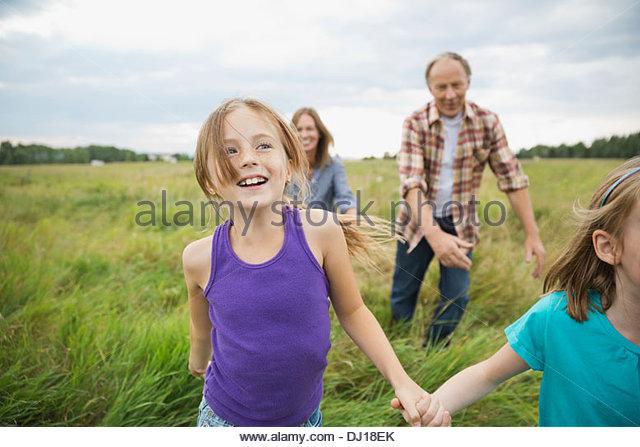 Grandparents chasing granddaughters in field - Stock-Bilder