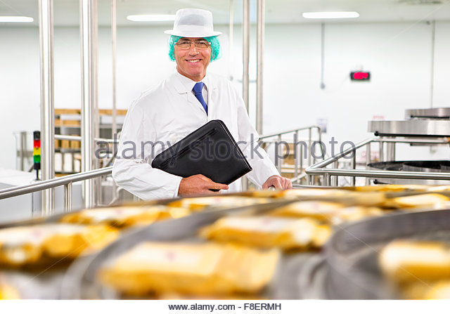 Portrait smiling bank manager at production line in cheese processing plant - Stock Image