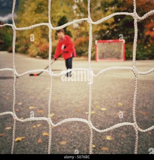 Young boy playing street hockey - Stock Image