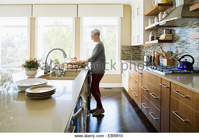 Woman cooking in kitchen - Stock Image