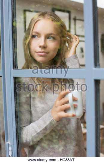 Young woman with coffee cup beside window. - Stock Image